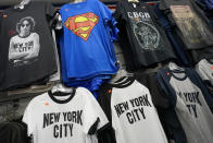 New York City souvenir T-shirts are on display for sale at a gift shop, Thursday, Nov. 12, 2020, in New York's Times Square. In souvenir shops from Times Square to the World Trade Center, shelves full of T-shirts and trinkets still love New York, as the slogan goes. But the proprietors wonder when their customers will, again. The coronavirus has altered many aspects of life and business in the United States' biggest city, and the pandemic is taking a major toll on the gifts-and-luggage stores that dot tourist-friendly areas. After setting records year after year since 2010, travel to New York has plummeted during the pandemic. (AP Photo/Mary Altaffer)