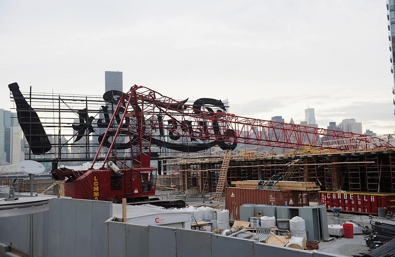 NEW YORK, NY - JANUARY 09:  A construction crane lies mangled behind a sign after it collapsed on January 9, 2013 in the Queens borough of New York City. The crane collapse injured seven construction workers on the site in the Long Island City neighborhood.  (Photo by Dimitrios Kambouris/Getty Images)