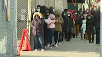 New Yorkers wait in line at a Covid-19 testing site in Queens as the city shutters its schools following an increase in coronavirus cases