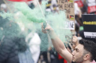 A man holds a flare as other hold placards and banners in London, Saturday, May 22, 2021, as they take part in a rally supporting Palestinians. Egyptian mediators held talks Saturday to firm up an Israel-Hamas cease-fire as Palestinians in the Hamas-ruled Gaza Strip began to assess the damage from 11 days of intense Israeli bombardment. (AP Photo/Alastair Grant)