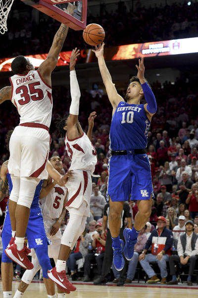 Kentucky guard Johnny Juzang (10) pulls up for a jump shot over Arkansas defenders Jimmy Whitt Jr.(33) and Reggie Chaney (35) during the second half of an NCAA college basketball game, Saturday, Jan. 18, 2020, in Fayetteville, Ark. (AP Photo/Michael Woods)