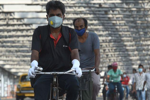 Commuters wear face masks as they cycle over Howrah Bridge at Howrah on June 3, 2020 in Kolkata.