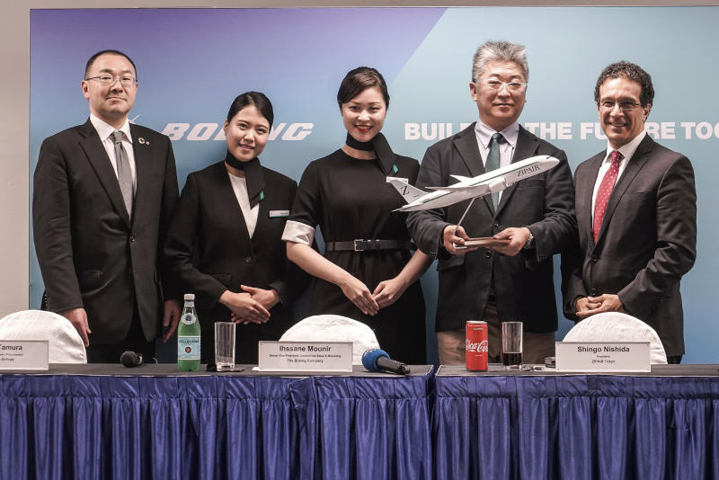 Members of the aviation industry, Boeing, Japan Airlines and ZipAir Tokyo pose for the media after a media conference during the Singapore Airshow  in Singapore Tuesday, Feb. 11, 2020. Singapore's air show began Tuesday with the usual ribbon cutting and displays of aerial prowess, but also with less typical warnings to industry and military figures attending to avoid handshakes and other close contact to avoid spreading a virus that has sickened tens of thousands of people. (AP Photo/Danial Hakim)