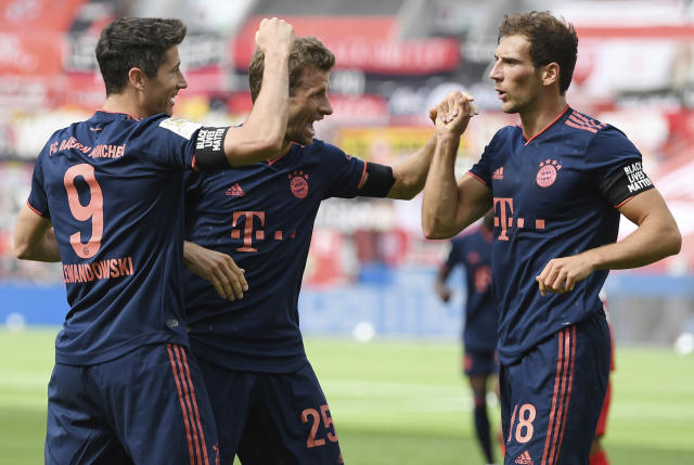 Robert Lewandowski, left, of Munich celebrates his team's fourth goal with teammates Thomas Mueller, center, and Leon Goretzka during the German Bundesliga soccer match between Bayer Leverkusen and Bayern Munich in Leverkusen, Germany, Saturday, June 6, 2020. (Matthias Hangst, Pool via AP)
