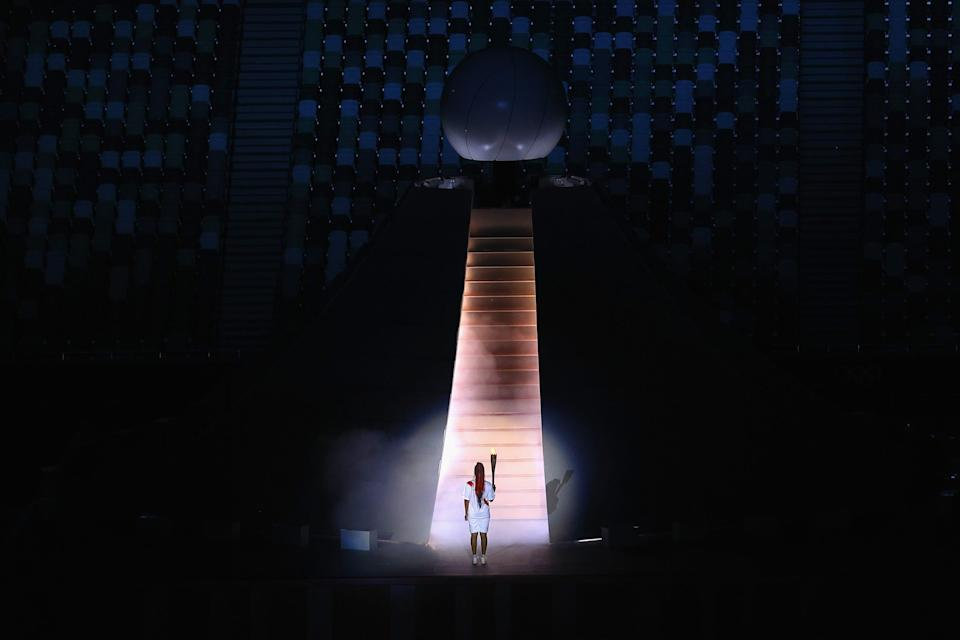 Naomi Osaka of Team Japan carries the Olympic torch towards the Olympic cauldron during the opening ceremony.