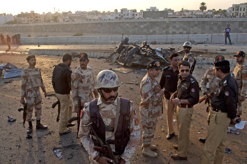 Members of Pakistani security agencies inspect the site of a bombing in Karachi, Pakistan, Thursday, Jan. 9, 2014. Police said a car bomb has killed a senior police investigator known for arresting dozens of Pakistani Taliban, as well as two other officers. (AP Photo/Shakil Adil)