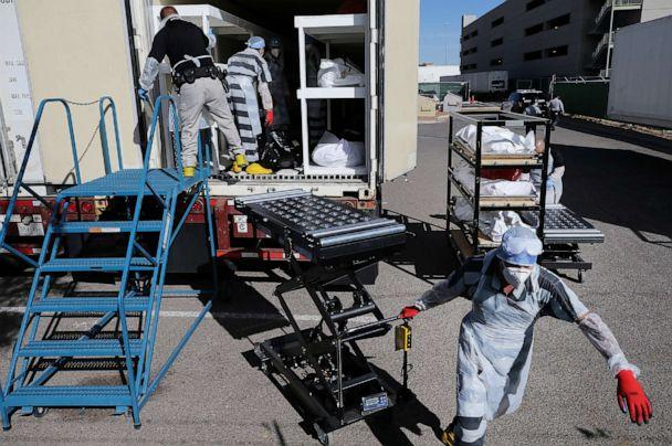 PHOTO: Inmates from El Paso County detention facility work loading bodies into a refrigerated temporary morgue trailer in a parking lot of the El Paso County Medical Examiner's office, Nov. 17, 2020 in El Paso, Texas. (Mario Tama/Getty Images)