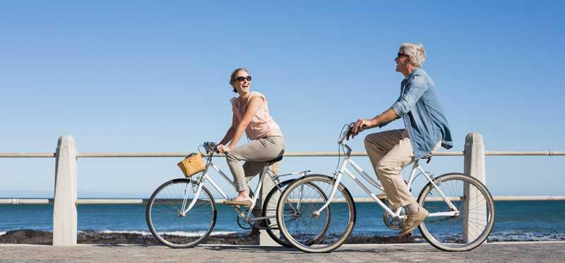 A couple riding bikes on a boardwalk by the beach.