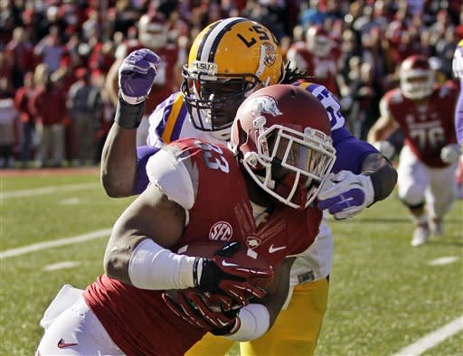 Arkansas running back Dennis Johnson (33) is tackled by LSU linebacker Lamin Barrow (57) in the first quarter of an NCAA college football game in Fayetteville, Ark., Friday, Nov. 23, 2012. (AP Photo/Danny Johnston)
