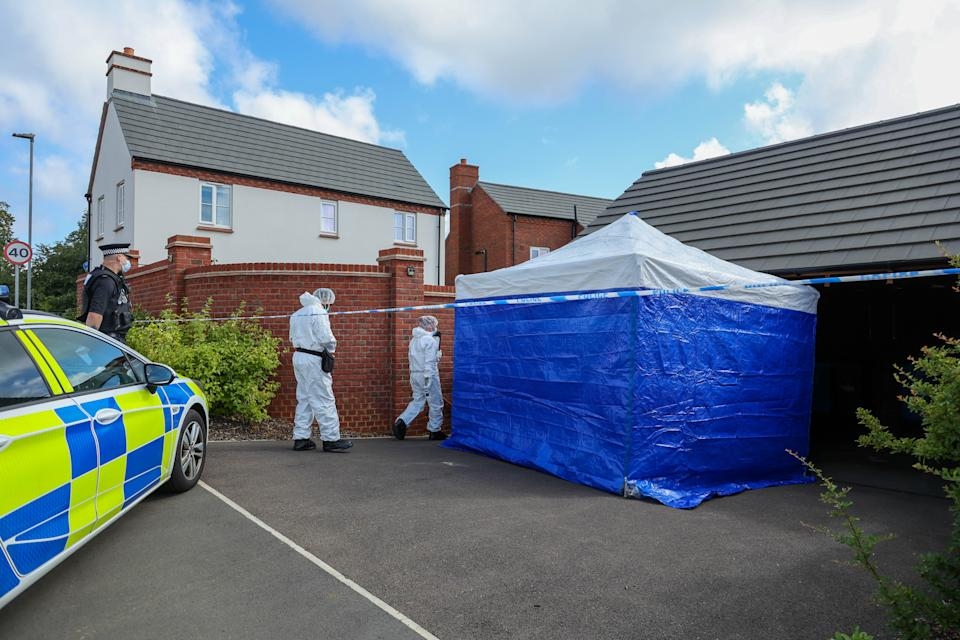 Police at the scene in Kettering following the discovery of two bodies on Friday. (SWNS)