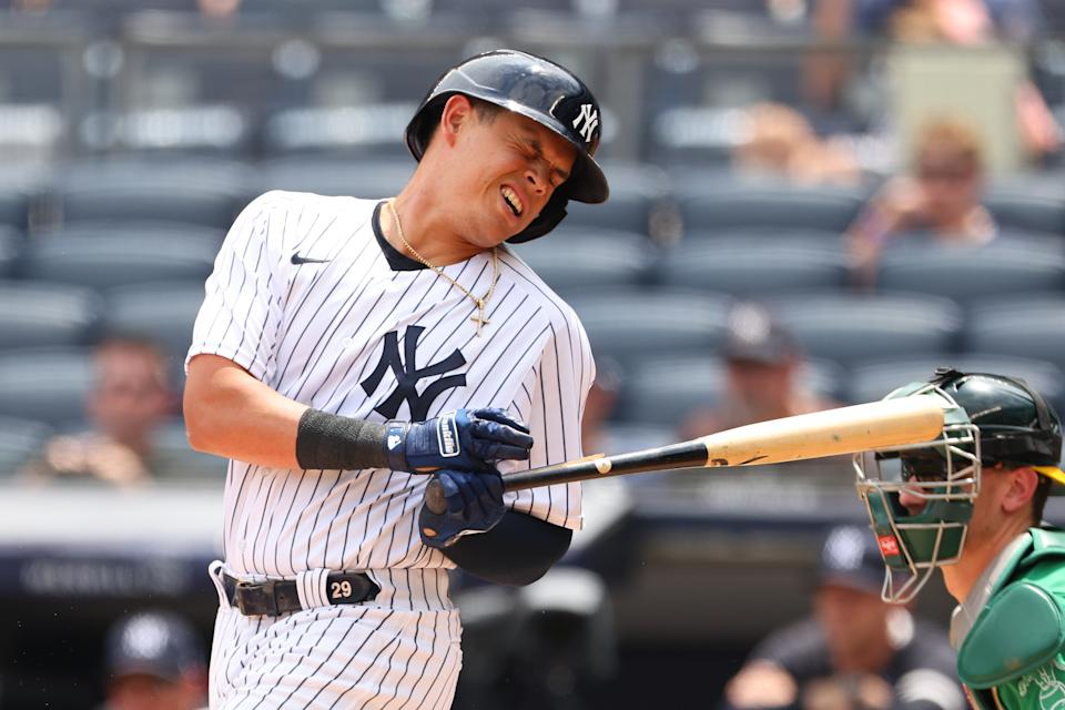 Gio Urshela of the New York Yankees is hit with a splinter part of the bat as he hits into a double play.