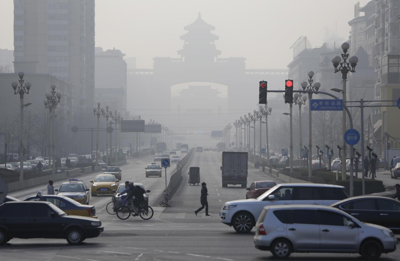 """Pedestrians cross the road near the Beijing West Railway Station (background) on a hazy day in Beijing, January 17, 2014. Beijing's mayor pledged on Thursday to cut coal use by 2.6 million tonnes and set aside 15 billion yuan ($2.4 billion) to improve air quality this year as part of the city's """"all-out effort"""" to tackle air pollution, state news agency Xinhua said. REUTERS/Jason Lee (CHINA - Tags: ENVIRONMENT POLITICS)"""