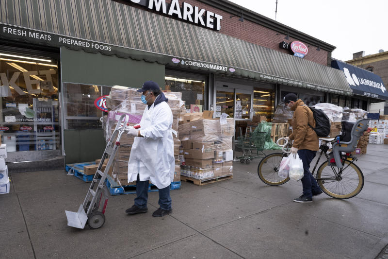 A worker and a customer wear masks outside Cortelyou Market, Friday, April 3, 2020 during the coronavirus pandemic in New York. (AP Photo/Mark Lennihan)