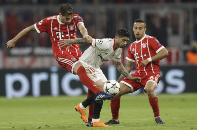 Bayern's Javi Martinez, left, and Sevilla's Ever Banega challenge for the ball as Bayern's Rafinha, right, looks on during the Champions League quarter final second leg soccer match between FC Bayern Munich and Sevilla FC at the Allianz Arena stadium in Munich, Germany, Wednesday, April 11, 2018. (AP Photo/Matthias Schrader)