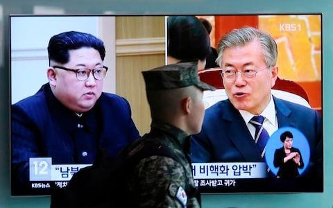 <span>TV screen showing file footage of South Korean President Moon Jae-in and North Korean leader Kim Jong Un</span> <span>Credit:  Ahn Young-joon/AP </span>