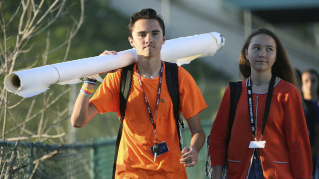 <p>Marjory Stoneman Douglas student David Hogg walks to school with a large rolled banner over his shoulder on Friday, April 20, 2018 in Parkland, Fla. (Photo: Amy Beth Bennett/South Florida Sun-Sentinel via AP) </p>