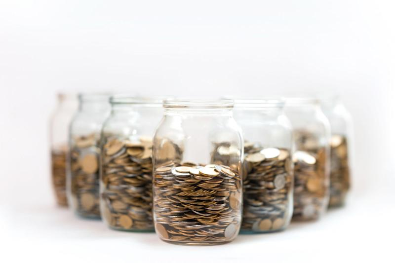 A group of glass jars filled with coins.