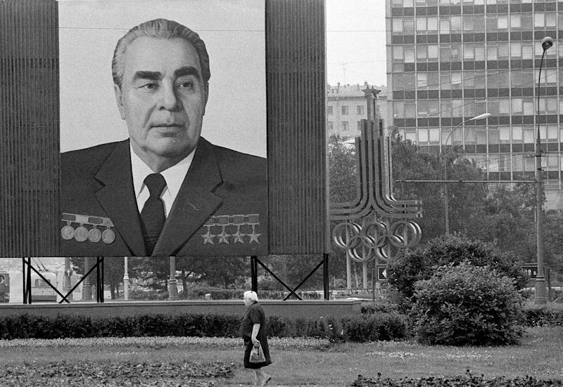 FILE - In this July 7, 1980 file photo, a woman walks past a huge portrait of Communist Party leader Leonid Brezhnev that dwarfs the symbol of the upcoming XXII Summer Olympics right behind, in Moscow. Brezhnev and his ruling Politburo wanted the games to legitimize the Soviet system, a military superpower and economic basket case. (AP Photo/File)