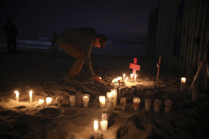 Candles are placed next to the border fence that separates Mexico from the United States, in memory of migrants who have died during their journey toward the U.S., in Tijuana, Mexico, late Saturday, June 29, 2019. (AP Photo/Emilio Espejel)