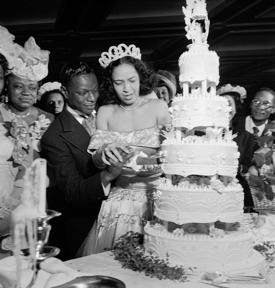 <p>Jazz singer Nat King Cole helped his new wife, Maria Hawkins, cut the five-tier wedding cake at their Harlem reception in 1948. The couple, dressed to the nines in a tailcoat tuxedo and an ivory off-the-shoulder satin ball gown, got married on March 28, 1948. </p>
