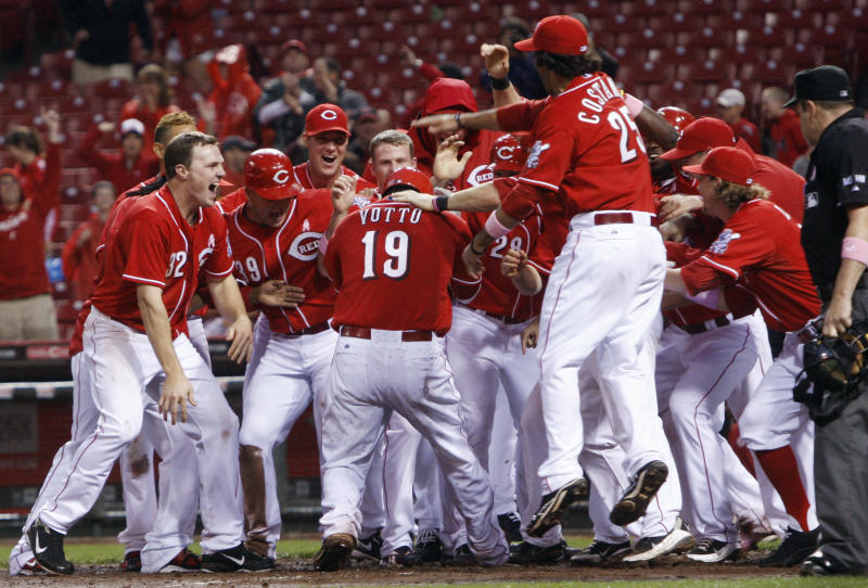 Cincinnati Reds' Joey Votto (19) is mobbed at the plate after hitting a grand slam off Washington Nationals relief pitcher Henry Rodriguez in the ninth inning of a baseball game, Sunday, May 13, 2012, in Cincinnati. Votto had three home runs as Cincinnati won 9-6. (AP Photo/Al Behrman)