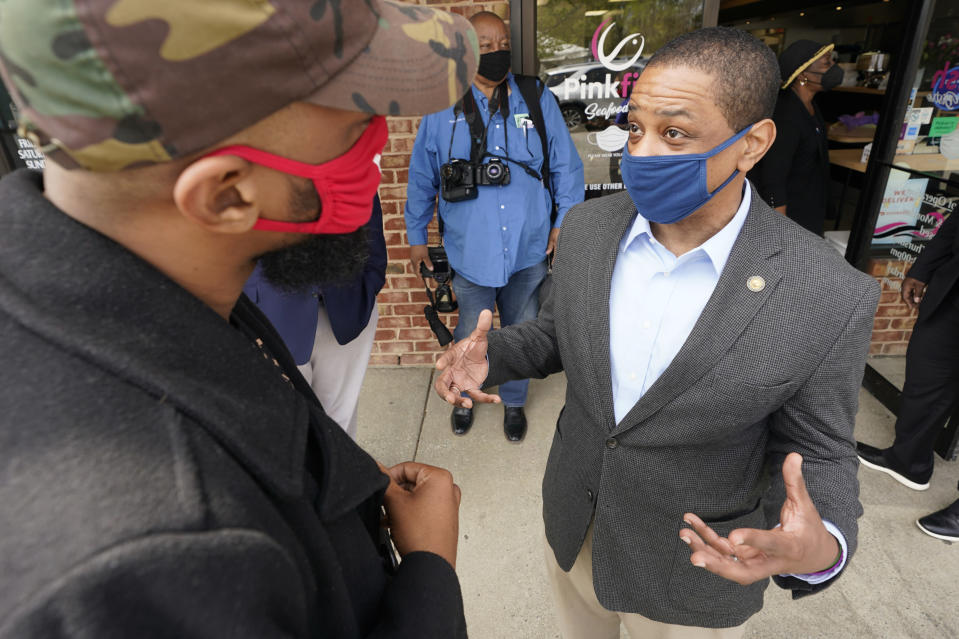 Virginia Democratic gubernatorial candidate Lt. Gov. Justin Fairfax, right, speaks to a supporter outside Pink Fish restaurant in Hampton, Va., Thursday, April 8, 2021. Fairfax has long had lofty political ambitions, and despite facing two unresolved allegations of sexual assault he's pressing forward with a bid for governor. (AP Photo/Steve Helber)