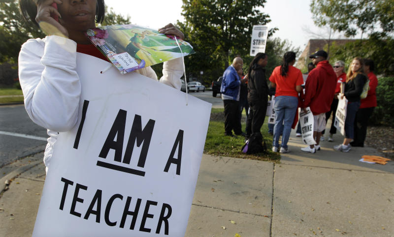 A handful of teachers picket outside Shoop Elementary School in Chicago, Monday, Sept. 17, 2012, as a strike by Chicago Teachers Union members heads into its second week. Mayor Rahm Emanuel said he will seek a court order to force the city's teachers back into the classroom. (AP Photo/M. Spencer Green)