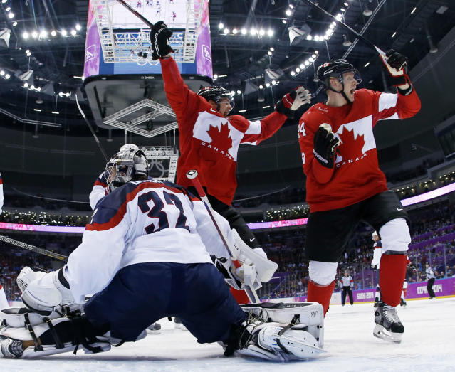 Canada forward Benn Jamie, left, reacts after scoring a goal in front of USA goaltender Jonathan Quick of a men's semifinal ice hockey game at the 2014 Winter Olympics, Friday, Feb. 21, 2014, in Sochi, Russia. (AP Photo/Julio Cortez, Pool)