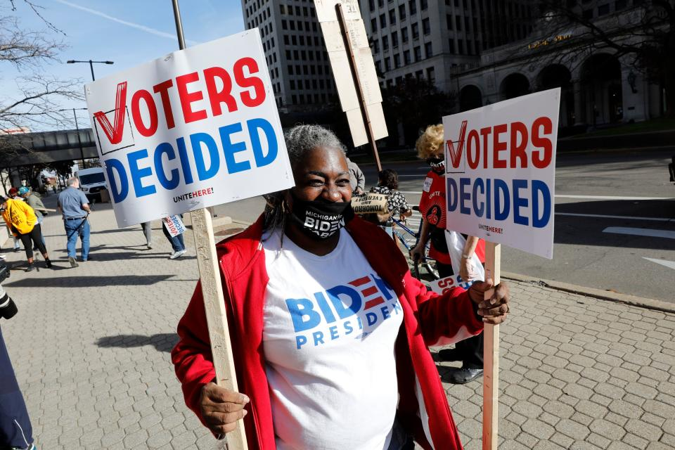 Zinnia Patcas hands out signs as people gather to celebrate Joe Biden's win in the presidential election on November 7, 2020 in Detroit, Michigan. (Jeff Kowalsky/AFP via Getty Images)