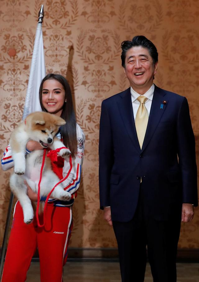 Russian figure skating gold medallist Alina Zagitova and Japanese Prime Minister Shinzo Abe pose with an Akita Inu puppy presented to Zagitova, in Moscow, Russia May 26, 2018. REUTERS/Maxim Shemetov