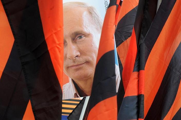 A protesters holds a portrait of Russian President Vladimir Putin behind flags of the ribbon of Saint George during a May Day rally in Saint Petersburg on May 1, 2015 (AFP Photo/Olga Maltseva)
