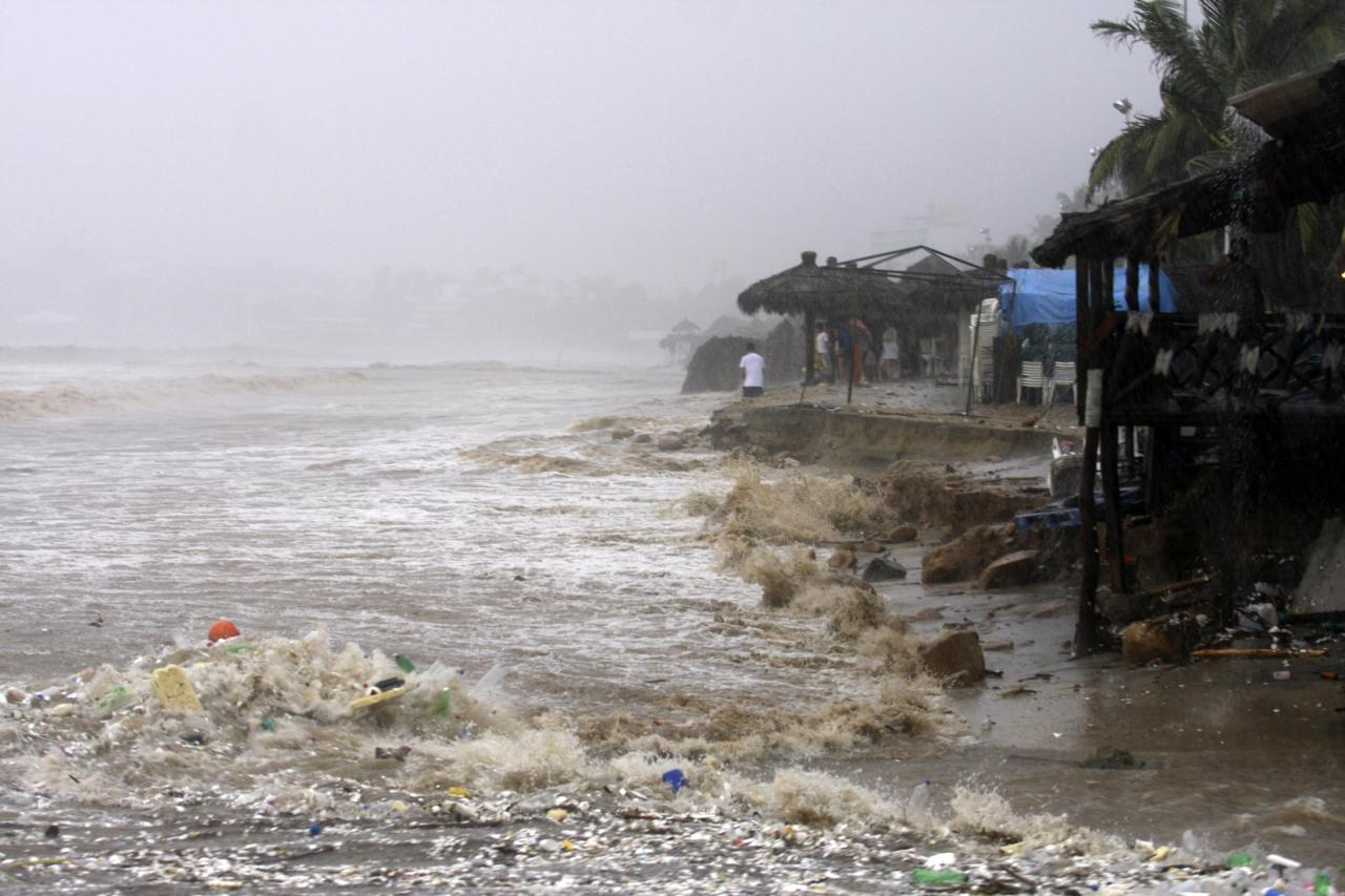 Waves flood a beach in Acapulco September 15, 2013. Hurricane Ingrid and tropical depression Manuel brought heavy rains to Mexico's Gulf and Pacific coasts on Sunday, causing flooding and landslides, killing 21 people and forcing some towns to cancel national Independence Day celebrations. REUTERS/Jacobo Garcia (MEXICO - Tags: DISASTER ENVIRONMENT)