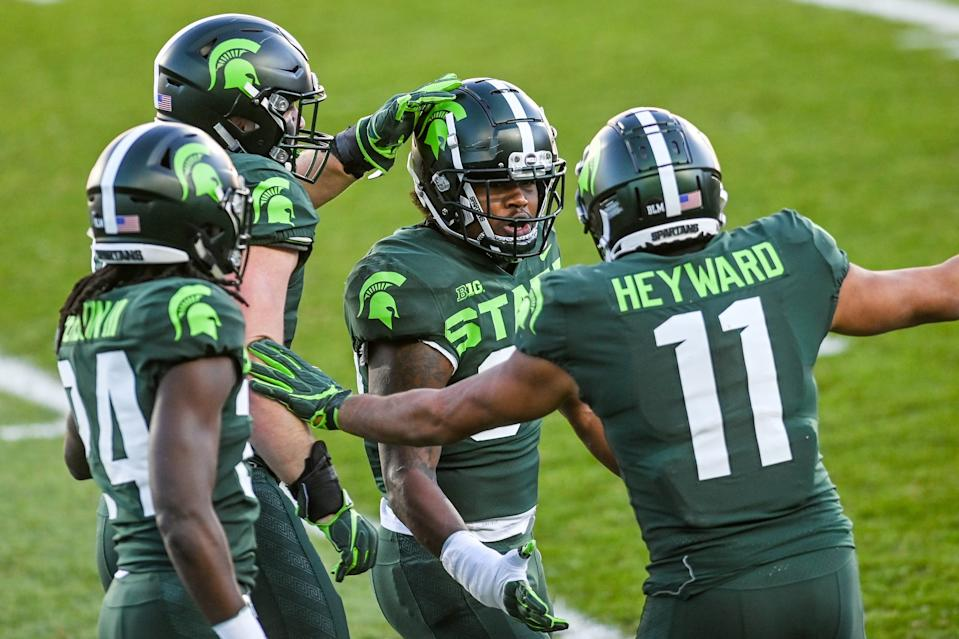 Michigan State's Antjuan Simmons, center, celebrates a stop with teammates including Connor Heyward, right, against Northwestern during the first quarter on Saturday, Nov. 28, 2020, at Spartan Stadium in East Lansing.