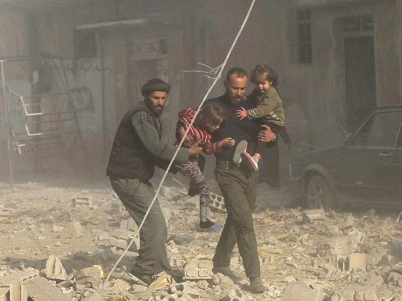 <strong>Nearly one in four civilians killed in Syria is a child, a report has found; Syrian men are seen carrying their children to safety following residential air strikes in Damascus, Syria, on December 3</strong> (Anadolu Agency via Getty Images)