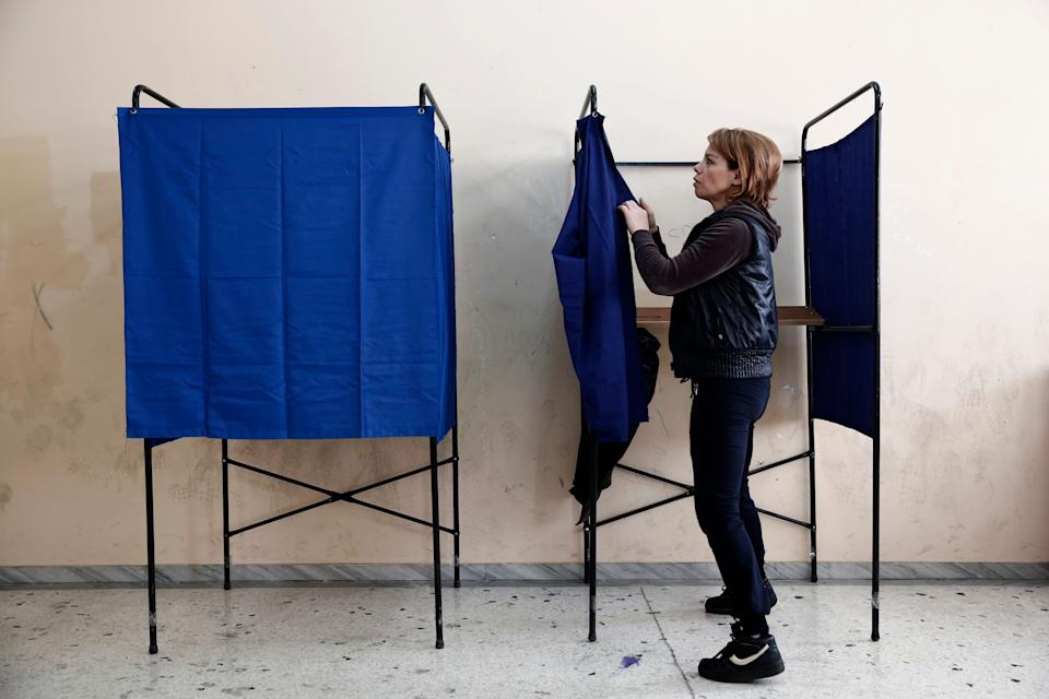 A municipal worker assembles voting booths at a voting center, in Athens, Friday, Jan. 23, 2015.  (AP Photo/Petros Giannakouris)