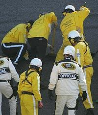 Officials work to repair a pothole in the middle of the Daytona 500 between Turns 1 and 2