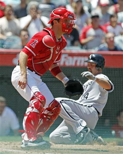Chicago White Sox's Paul Konerko, right, scores past Los Angeles Angels catcher John Hester in the third inning of a baseball game in Anaheim, Calif., Thursday, May 17, 2012. (AP Photo/Reed Saxon)