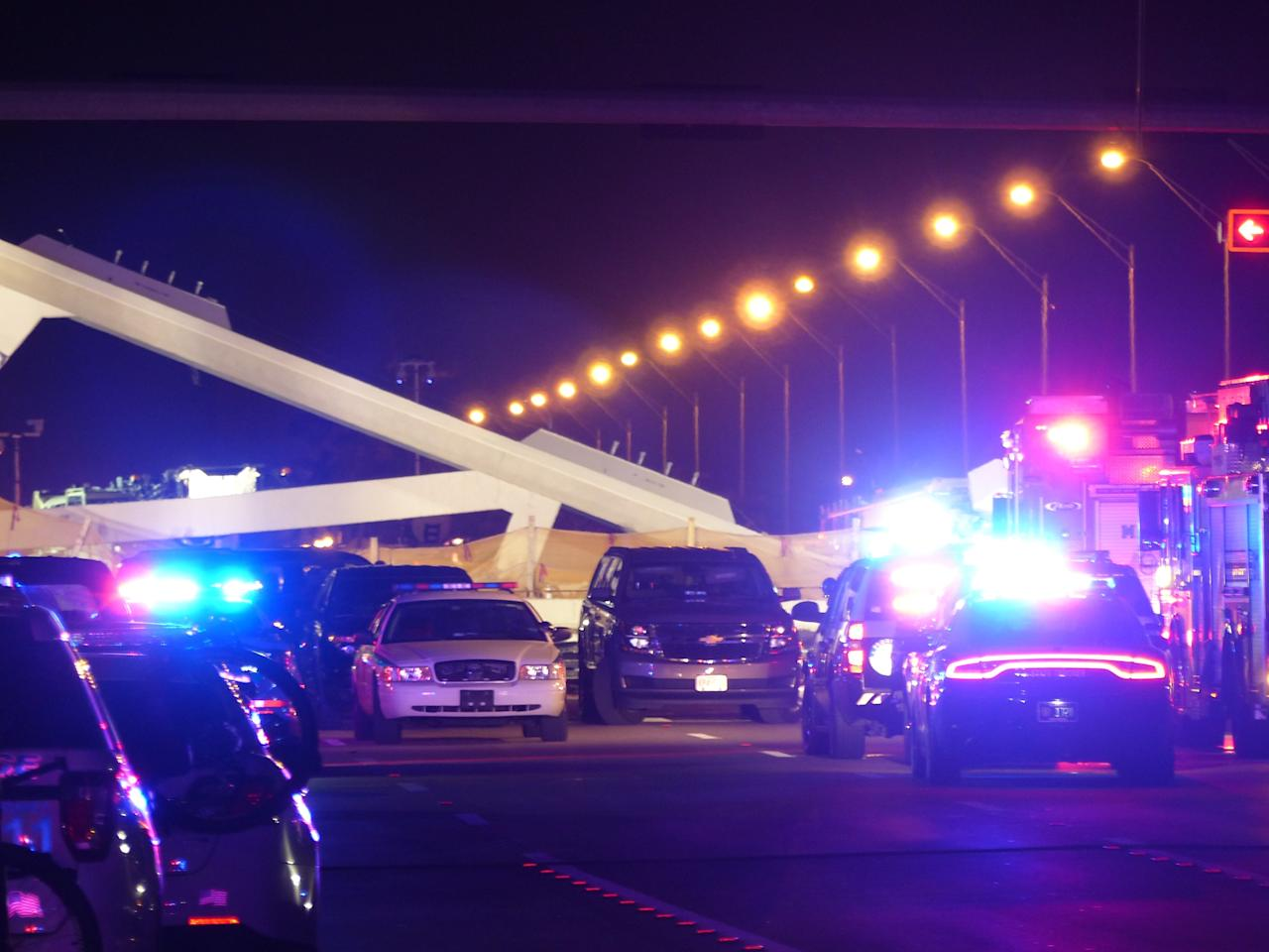 <p>Police lights illuminate the scene of a pedestrian bridge collapse in Miami, Florida on March 15, 2018, crushing a number of cars below and reportedly leaving several people dead. (Photo: Gaston De Cardenas/AFP/Getty Images) </p>