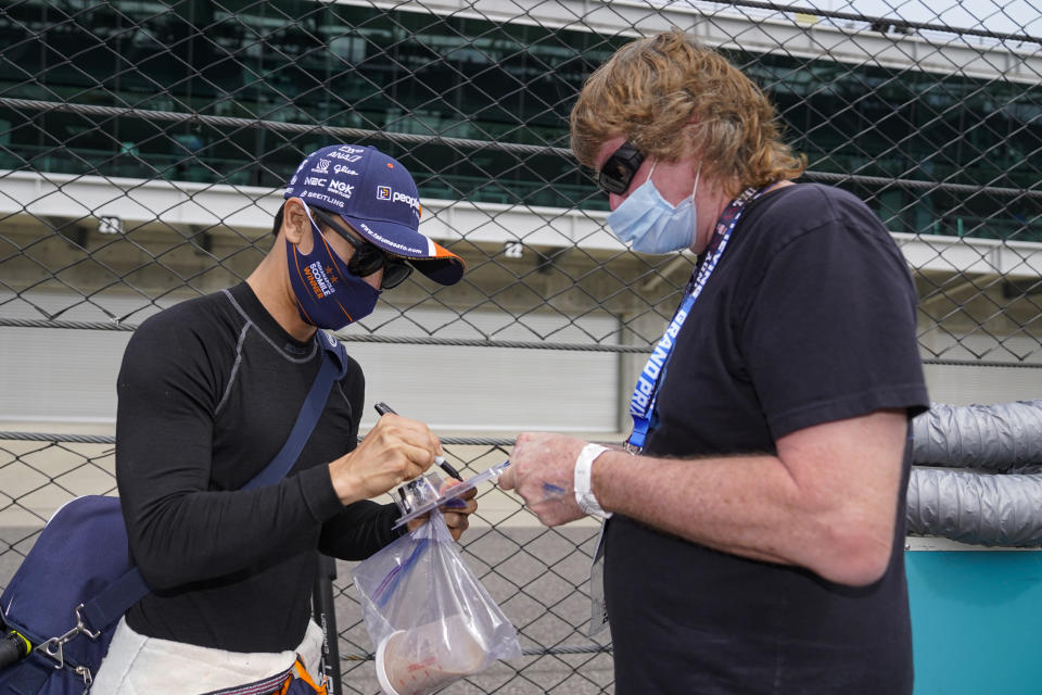 Takuma Sato of Japan signs an autograph for a fan during practice for the Indianapolis 500 auto race at Indianapolis Motor Speedway in Indianapolis, Tuesday, May 18, 2021. (AP Photo/Michael Conroy)