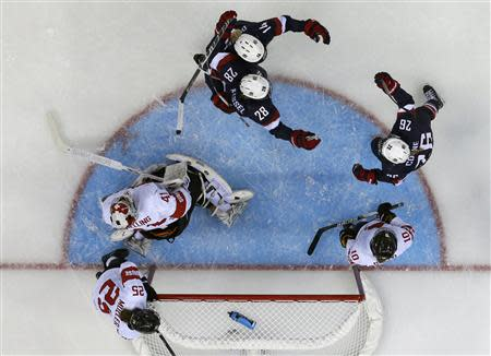 Team USA's Coyne celebrates her goal with teammates Kessel and Decker as Switzerland's goalie Schelling with teammates Muller and Bullo react during the third period of their women's preliminary round hockey game at the Sochi 2014 Winter Olympic Games