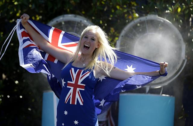 A spectator cools down in front of a fan spraying cool water while holding the Australian flag during day two at the Australian Open tennis championship in Melbourne, Australia, Tuesday, Jan. 14, 2014. Temperatures hit 40 Celsius (104 Fahrenheit) early afternoon and is expected to rise. (AP Photo/Aijaz Rahi)