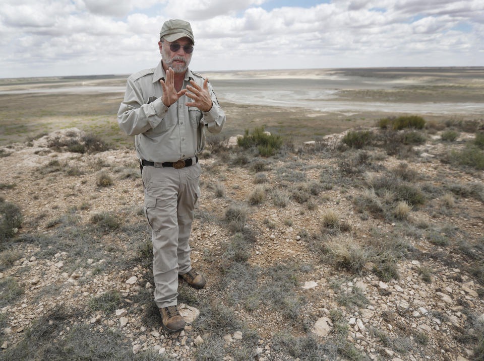 Biologist Jude Smith stands on a bluff overlooking an empty saline lake at the Muleshoe National Wildlife Refuge outside Muleshoe, Texas, on Tuesday, May 18, 2021. The lakes are fed by the Ogallala Aquifer, which has been become increasingly dry because of irrigation and drought. (AP Photo/Mark Rogers)