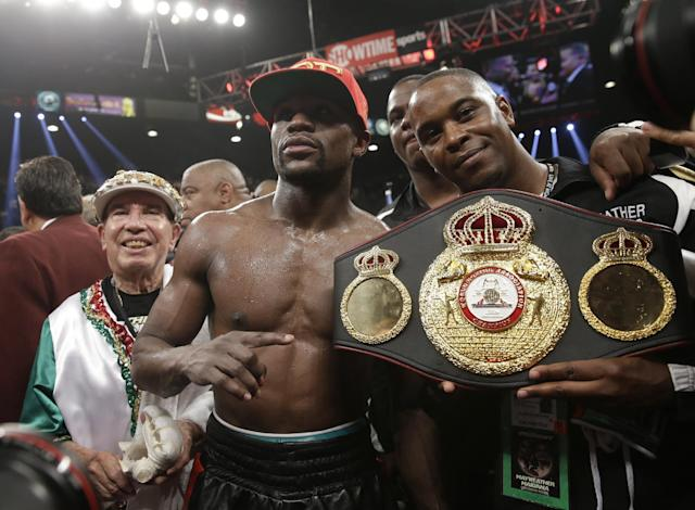 Floyd Mayweather Jr., center, poses with his corner and a champion's belt after his WBC-WBA welterweight title boxing fight against Marcos Maidana Saturday, May 3, 2014, in Las Vegas. Mayweather won the bout by majority decision. (AP Photo/Isaac Brekken)