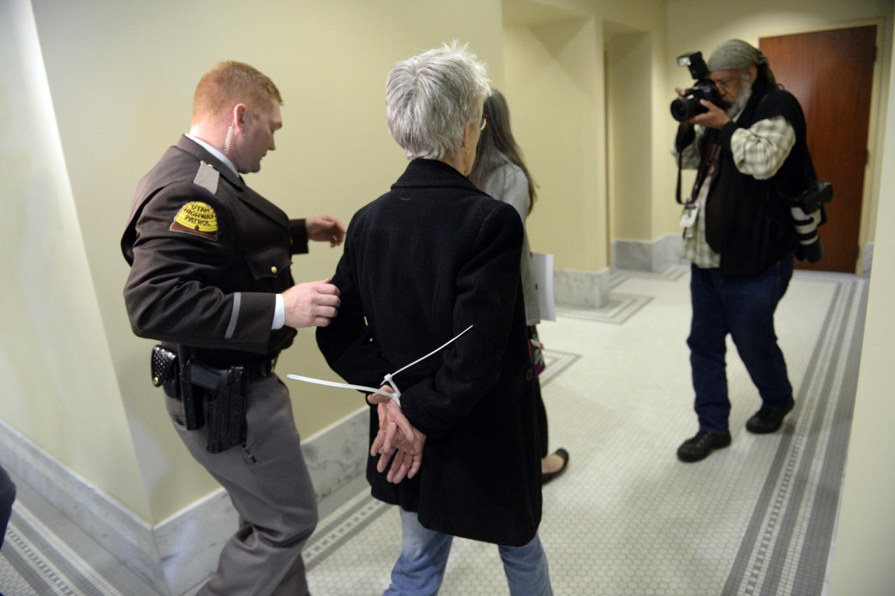 Gail Murdock, center, is arrested after blocking the doors to a committee meeting room at the Utah Capitol in Salt Lake City on Monday, Feb. 10, 2014. Utah Highway Patrol troopers, which provide Capitol security, led the protesters out in three waves after they blocked Senator Stuart Reid, R-Ogden, and visitors from two sets of double doors to the room. Protesters are calling for a statewide anti-discrimination law that includes sexual and gender orientation protections. (AP Photo/The Salt Lake Tribune, Francisco Kjolseth) DESERET NEWS OUT; LOCAL TV OUT; MAGS OUT
