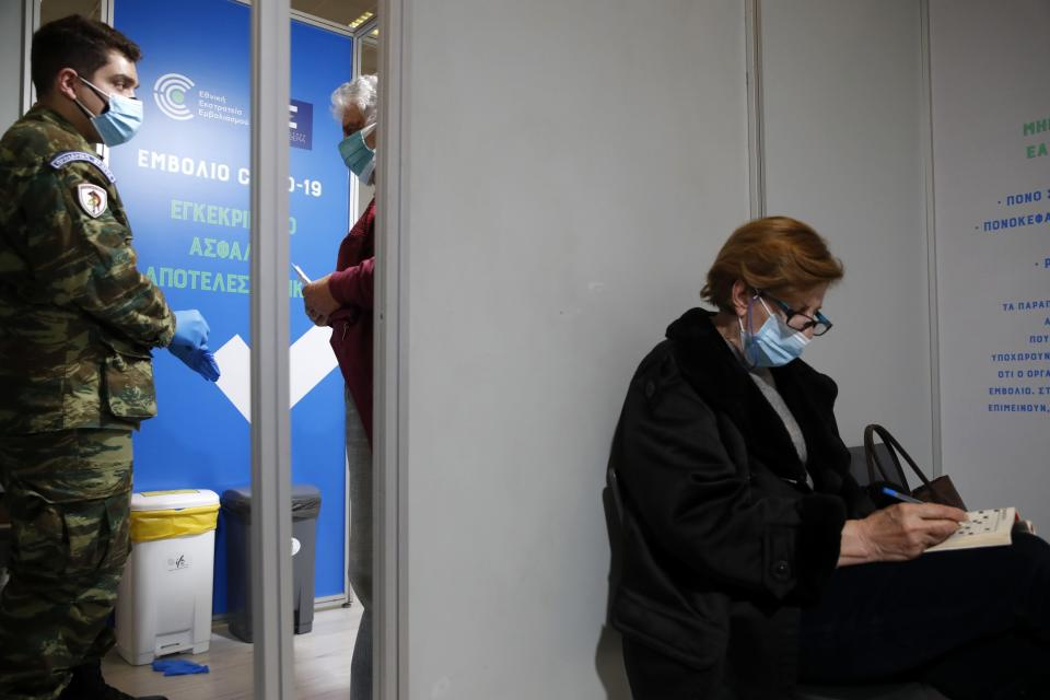 A woman solves a crossword puzzle as a military medical staff instructs Michalis Tzouanos, 76, after the second dose of Moderna vaccine at Promitheas vaccination mega center in Athens, Friday, March 19, 2021. More than 1.35 million doses of the COVID-19 vaccine have been administered so far in Greece, but daily infections remain on the rise despite four months of lockdown measures. (AP Photo/Thanassis Stavrakis)