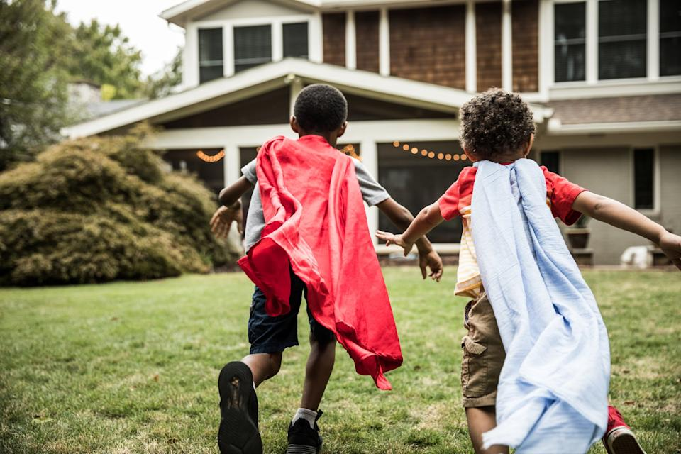 Young boys (3 yrs and 6yrs) in capes playing in backyard