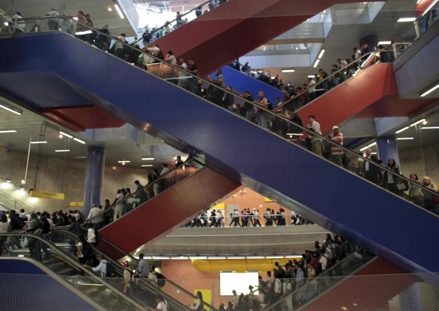 Commuters travel on escalators at a subway station in Sao Paulo May 21, 2014. Bus drivers in Sao Paulo went on strike for a second day on Wednesday, snarling transit and leaving hundreds of thousands stranded in South America's largest city less than a month before it hosts the opening World Cup soccer match. REUTERS/Chico Ferreira (BRAZIL - Tags: SPORT SOCCER WORLD CUP TRANSPORT CIVIL UNREST)