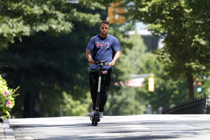 A man rides a electric scooter Thursday, Aug. 8, 2019, in Atlanta. Atlanta is banning electric scooters during nighttime hours during a deadly summer for riders. In Atlanta, three riders have died since May in crashes that involved a public bus, an SUV and a car. Police in the Atlanta suburb of East Point say a fourth rider was killed there Tuesday in a collision involving his scooter and a truck. (AP Photo/John Bazemore)