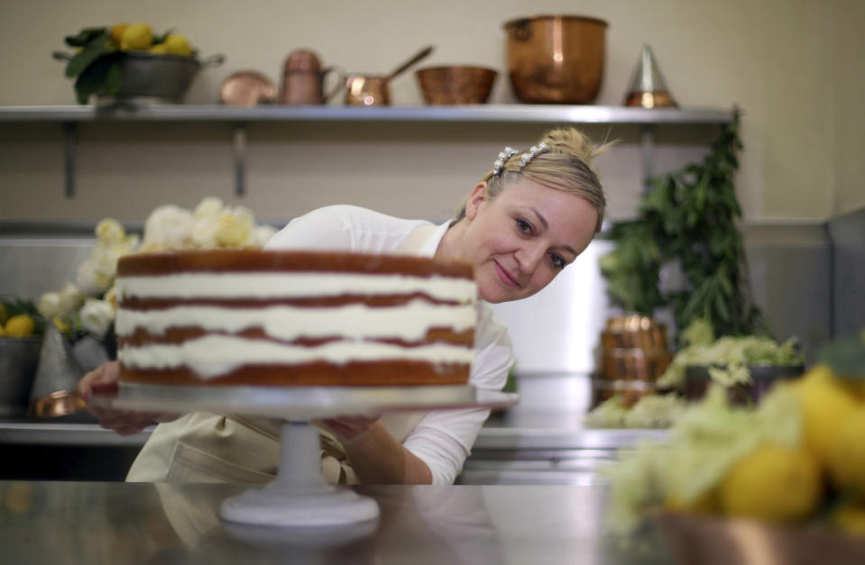 Claire Ptak, owner of Violet Bakery puts the finishing touches to one tier of the cake for the wedding of Prince Harry and Meghan Markle in the kitchens at Buckingham Palace.