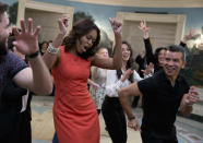 """<p>To get down to Gloria Estefan's """"Conga,"""" Michelle Obama wore a red hot dress, which she accessorized with an armful of silver bracelets. <i>Photo: AP</i><br></p>"""